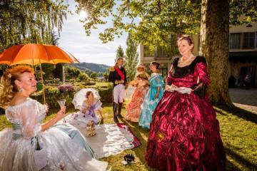 Kostümgruppe beim Picknick im Park